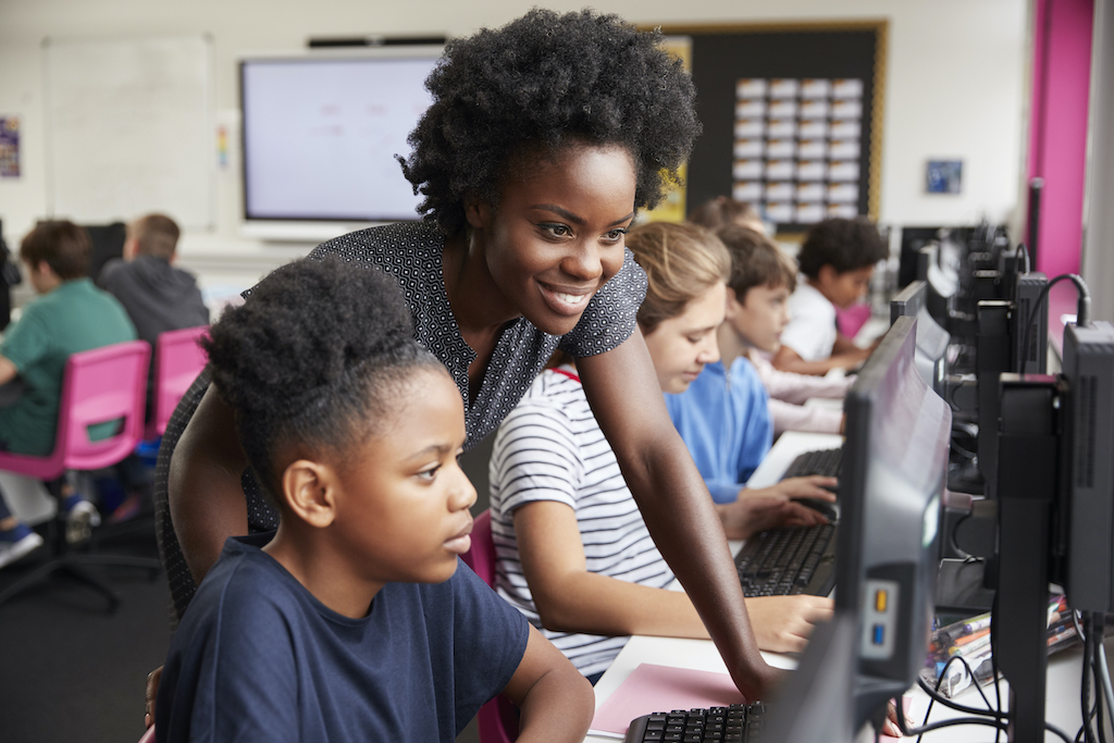 African American female teacher Helping Female Pupil Line Of High School Students Working at Screens In Computer Class