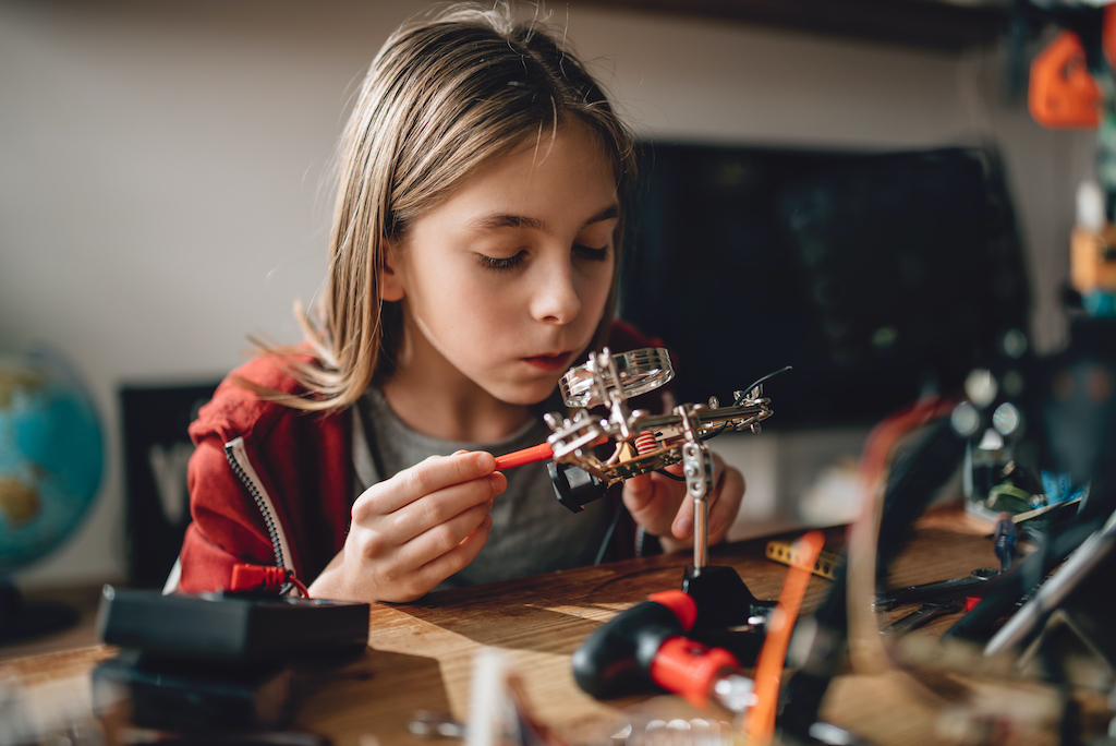 Caucasian girl wearing red hoodie looking circuit board throughout magnifying glass at home and building a robot