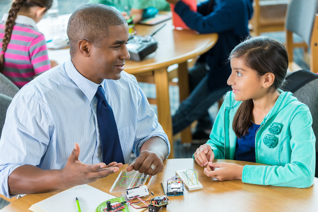 Mid adult African American man is teaching a young Hispanic girl in a public school library. Student and teacher are using robotics kits. Diverse students are working on a project in background.